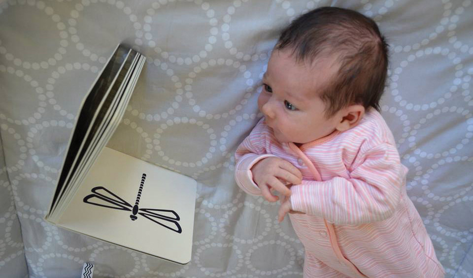 baby looking at black and white book