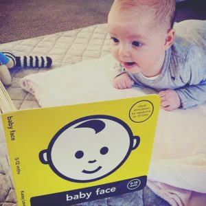 Baby doing tummy time with Baby Face book