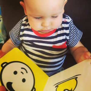 Baby reading Baby Face high-contrast board book